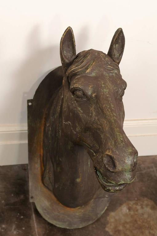 This exquisite horse head sculpture from the mid-20th century features a cast iron head mounted on an oval backplate. Very detailed, the horse features great realism with its opened mouth. Perfect to be mounted on the wall, the backplate has four