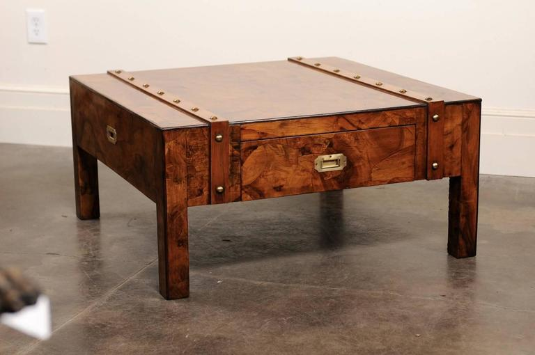 This English Campaign coffee table from the mid-20th century features an exquisite burled wood top over a single drawer. The top is adorned with two wooden bands with brass nailheads, reminiscent of the leather straps of a trunk or suitcase. The