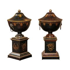 Pair of French 1920s Tole Black Tole Urns on Pedestals with Gilded Accents