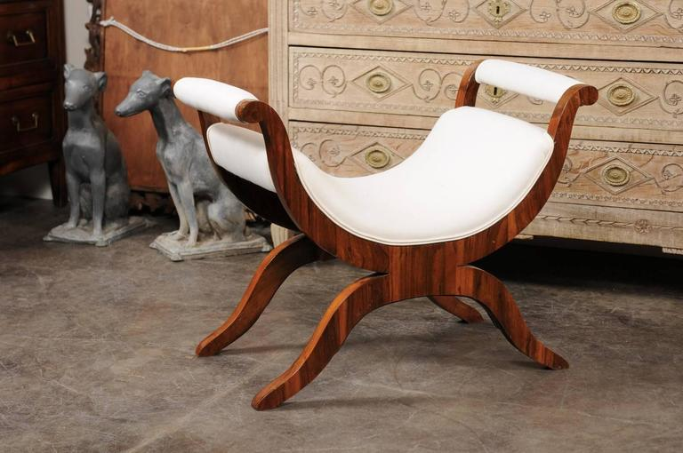 This exceptional Biedermeier bench was born in Vienna in the first quarter of the 19th century. Featuring a very elegant Silhouette without-scrolled upholstered arms, the bench is raised on a beautiful Curule style base. We can see here the subdued