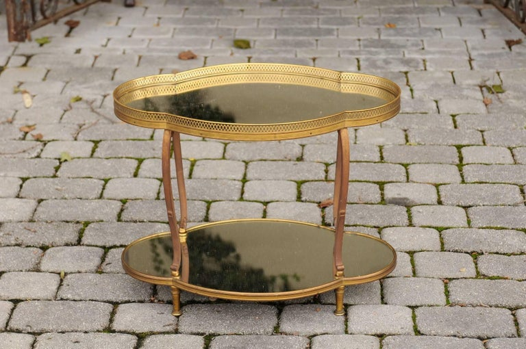 A French two-tiered Maison Jansen style brass and mirror side table from the mid-20th century. This French quatrefoil table features a brass and iron armature securing two levels of elongated clover-shaped mirrored shelves. The top is adorned with a