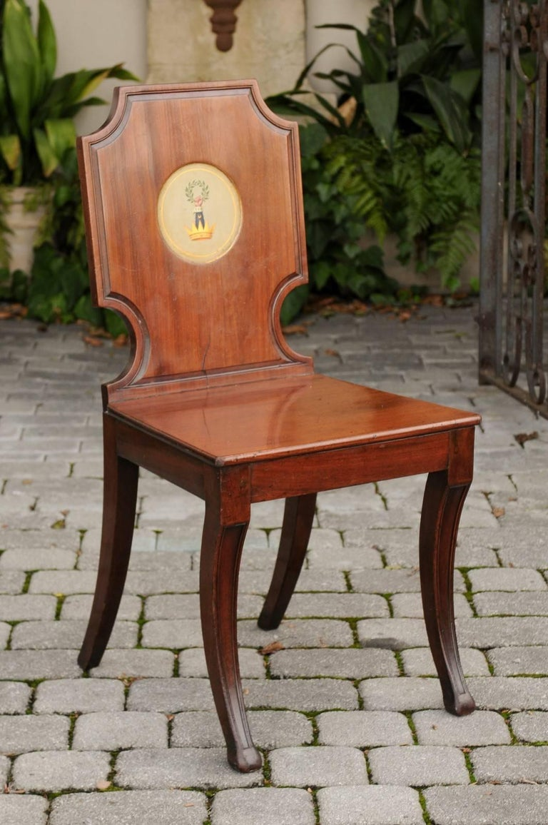 An English wooden hall chair with plank seat and painted crest from the mid-19th century. This English hall chair features a slightly slanted cartouche-shaped back, adorned in its center with medallion depicting a crest made of a crown, from which