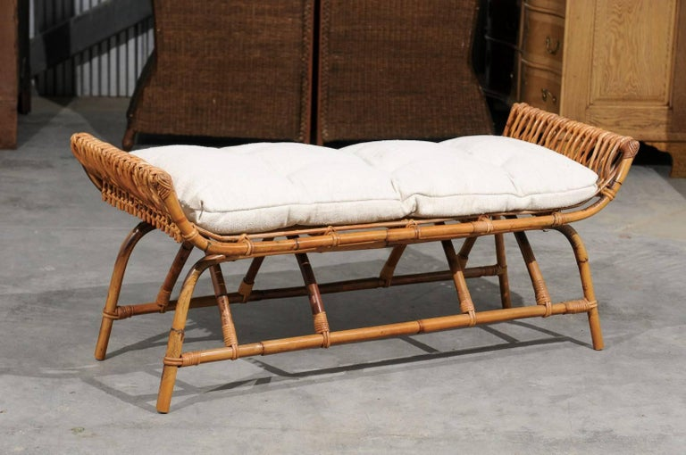 A French midcentury rattan low bench upholstered with Belgian linen cushion. This French rattan bench from the mid-20th century features a rattan structure made of simple curves. The rectangular seat is flanked by two curving arms. A new custom-made