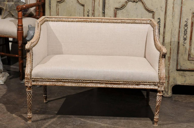 A French Louis XVI style petite wooden bench with distressed paint and linen upholstery from the 1820s-1840s. This French small bench features a straight back and scrolled arms framing a rectangular seat. The back, solid arms and seat are covered in