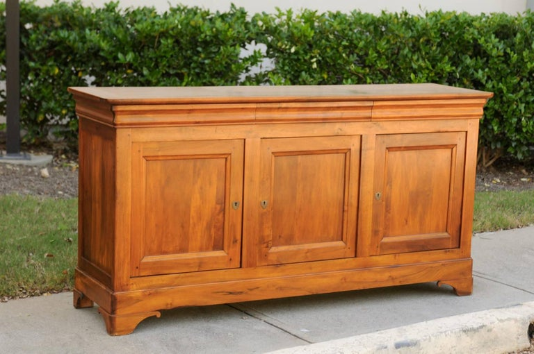 A French wooden enfilade with three drawers over three doors from the early 20th century. This French long buffet features a rectangular planked top over three dovetailed drawers, ingeniously hidden in the apron. Three doors with recessed panels