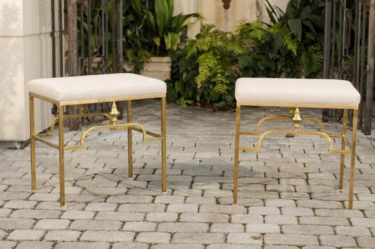 A pair of Italian Mid-Century Modern brass stools with new linen upholstery. Each of this pair of vintage Italian stools features a rectangular linen-covered seat, resting on an Art Deco style brass armature. The clean lines of the base are