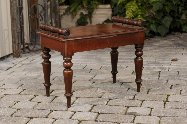 An English petite mahogany hall bench with cylindrical supports and turned legs from the second half of the 19th century. This English hall bench features a rectangular single planked seat, flanked with cylindrical lateral supports. The bench is