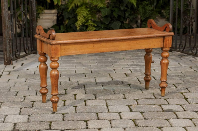 An English oak hall bench with turned legs and curled arm supports from the turn of the century. This English oak hall bench features a rectangular single plank wooden seat with beautiful grain, adorned with two exquisite curled arm supports. The
