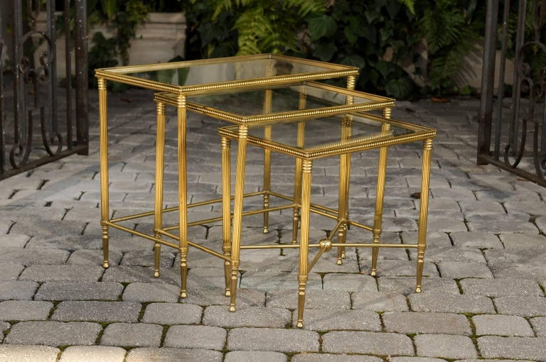 A set of three French nesting tables with glass tops and brass armature from the mid-20th century. Each of this charming set of French vintage nesting tables features a 1.75 thick glass top adorned in its surround with a mirrored frame and supported
