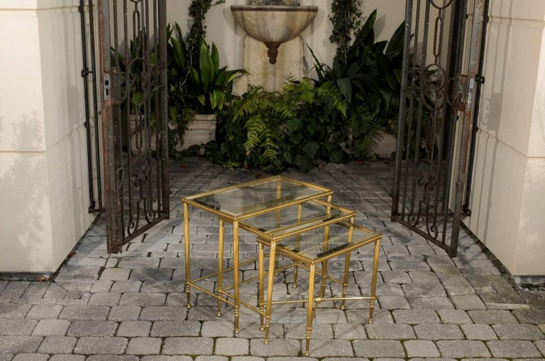 Mid-Century Modern Set of Three 1950s French Brass and Glass Nesting Tables with Beaded Trim For Sale