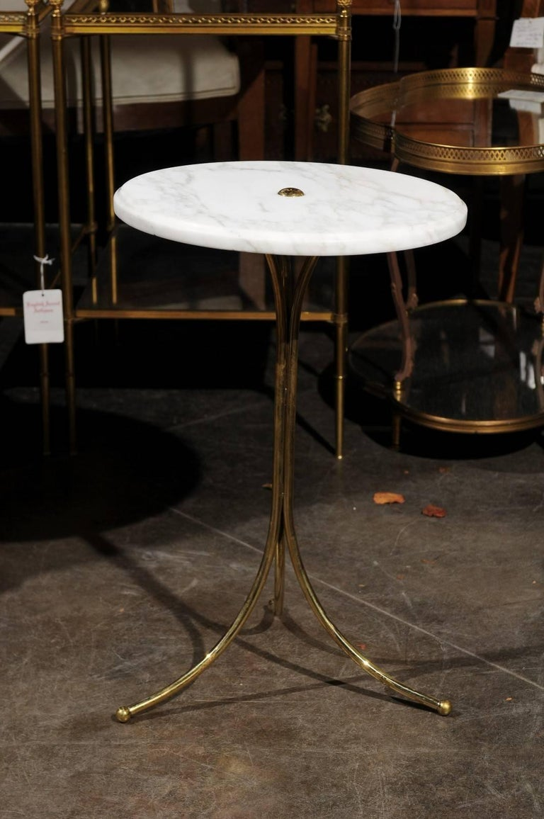 An Italian marble and brass drinks table from the Mid-Century Modern period. This Italian drinks table features a circular white marble top sitting above a brass pedestal base with splayed tripod base. The beauty of the marble top is only