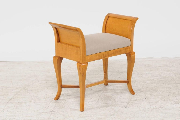 An Austrian Biedermeier petite maple wood upholstered window seat without-scrolled arms and cross stretcher from the mid-19th century. Born during the Biedermeier period that animated Austria and Germany in the first half of the 19th century, this
