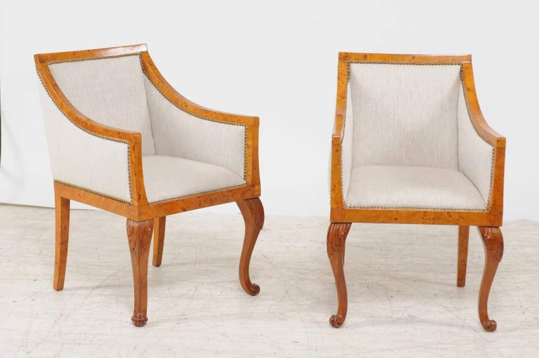 A pair of mid-19th century Biedermeier Austrian burled wood bergère chairs with new linen upholstery and brass nailhead trim. Each of this pair of Austrian armchairs features the typical traits of the Biedermeier period. The burled blond wood and
