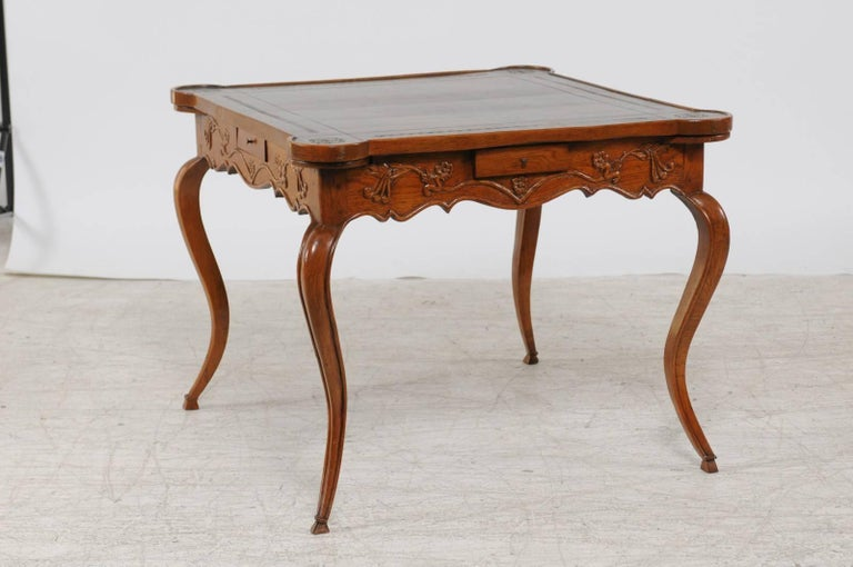 A French Louis XV style carved oak centre table with leather top, four drawers and pull outs from the second half of the 19th century. This French game or centre table features an embossed leather top with Greek key motifs, adorned with rounded