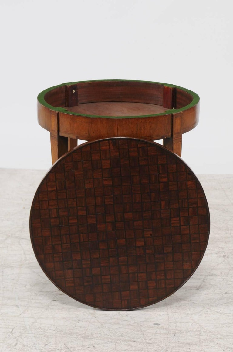 A French Louis XVI style round parquetry top game table with flip top and tapered legs from the second half of the 19th century. This French table features a circular parquetry top that flips to reveal a green felt lined side perfect for a game