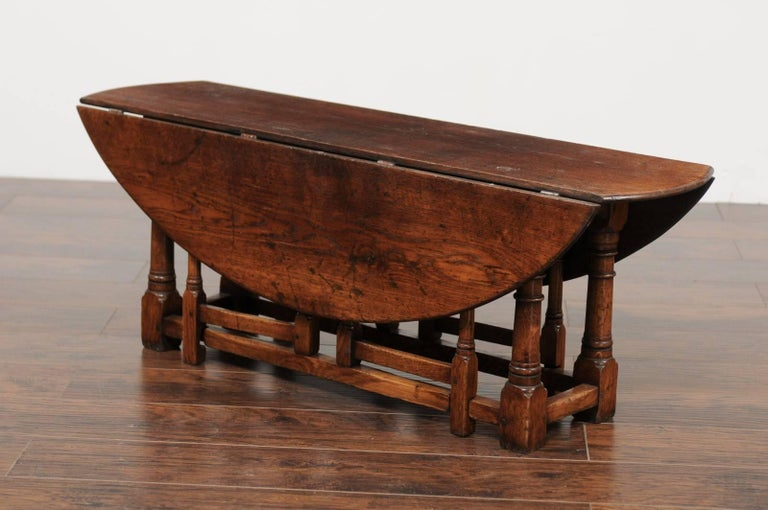 An Unusual English Oak Oval Top Drop Leaf Coffee Table With Double Gateleg From The