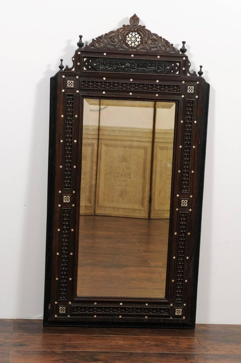 A pair of tall hand-carved Syrian mirrors with mother-of-pearl inlay and ebonized wood accents from the early 20th century. Each of this pair of Syrian mirrors features an exquisite frame. The triangular crest is adorned with a central star-shaped