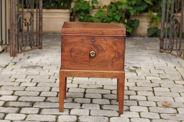 An English mahogany cellarette from the mid-19th century with custom Stand. This lovely English cellarette features a rectangular hinged top, adorned with an elegant oval banding. This lid opens thanks to a petite key to reveal a nicely