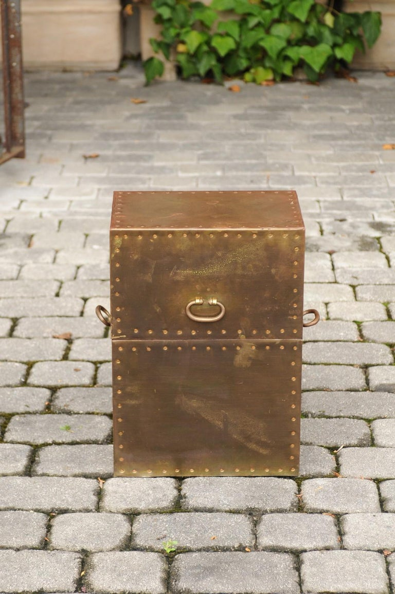 A large vintage English brass-plated box from the mid-20th century with handles and stud trim. This elegant English brass box is topped with an oblique-shaped lid connected to the rest of the body with a gilt chain, that opens thanks to a frontal