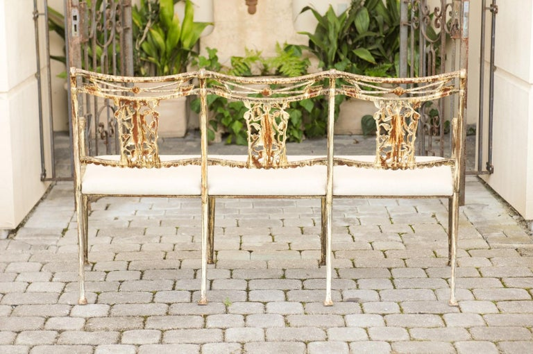 A Molla painted wrought iron upholstered garden bench from the mid-20th century depicting Diana, goddess of the hunt and her arrows. Created in the midcentury, this exquisite iron bench features a nicely weathered painted finish. Revealing its