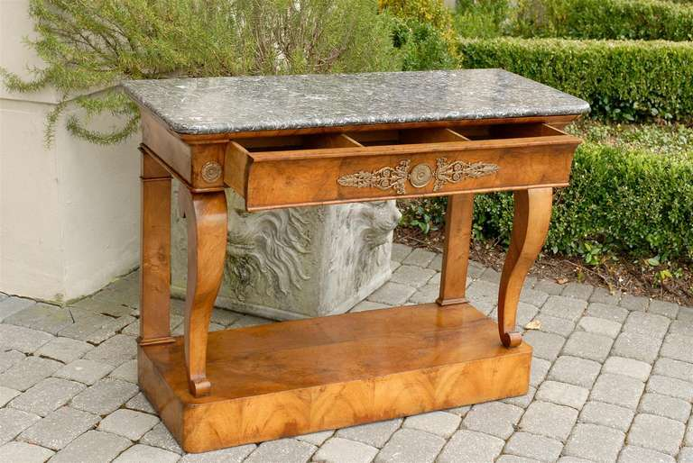 A mid-19th century French burl walnut Louis-Philippe console table with a rectangular variegated grey marble top over a doucine bronze-mounted frieze drawer. Two bronze carved rosettes flank the pull-out drawer divided in three-compartments and