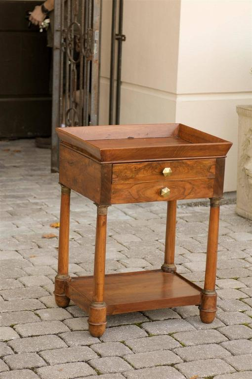 This French Empire walnut side table features a rectangular tray top over two thin drawers, one in the front and one in the back. To maintain a harmonious symmetry, the artist has ingeniously placed a faux drawer on each side to compliment the real
