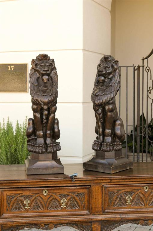 A pair of large English wooden carved lions from the late 1800s. These large English lions from the late 19th century are made of carved wood. The precision of the carving is quite impressive, the lions' manes are very detailed, and the instrument