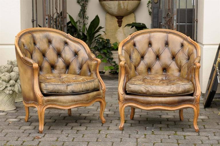 This pair of French Louis XV style bergeres features lovely colored leather upholstery, tufted in the back with nailhead trim. The wraparound backs, as well as the seat cushions, offer great comfort to the sitter. The curviness, typical of the Louis