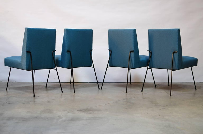 Beautiful set of four iron framed dining chairs inspired by the designs of Milo Baughman. Features an extremely comfortable floating seat comprised of springs and foam with a solid iron frame and oxidized brass glides. Newly covered in Maharam