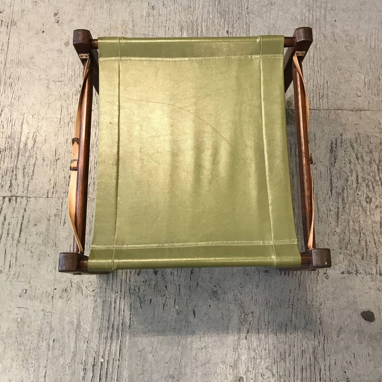 Break down camping / campaign ottoman by Gold Medal Folding Furniture, designed to come apart and roll up into a compact unit, green vinyl fabric cover and two canvas straps attached to the wooden frame.