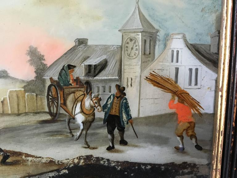 A charming églomisé painting (reverse painting on glass), circa 1800, in its original frame, depicting a village scene, probably French.