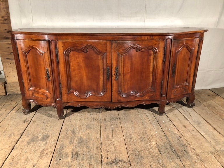 A fine quality Louis XV period enfilade buffet in fruitwood, circa 1760. Beautifully carved and constructed, with gracefully curved and paneled doors, scalloped apron and escargot feet, the piece retains its original iron hardware and wood top.