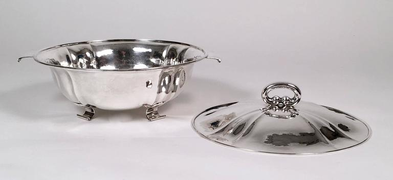 A very fine quality handmade Swiss sterling silver covered tureen, of circular form, with hand-hammered cover and base, both of which have decorative ribbing, with oval loop handle on the cover and flattened scrolled strap handles and feet. Signed