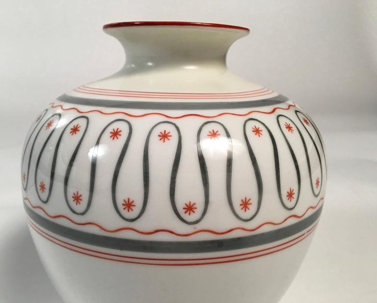 An Art Deco period German white porcelain vase decorated with thin hand-painted bands of gray and orange, centered by a serpentine gray band, with orange stars interspersed. Made by the Friedrich Kaestner, Saxonia porcelain factory, circa 1930s.