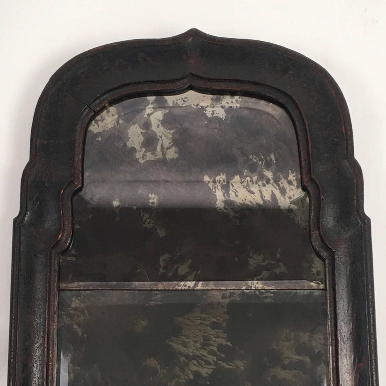 An early Queen Anne period black japanned, or lacquered, chinoiserie decorated mirror, the bracketed arched top over a rectangular lower half, the frame with wonderful bold form and old leathery patina, retaining traces of its original gold painted