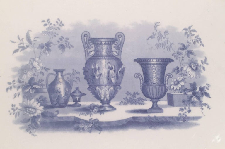 A blue and white rectangular Staffordshire pottery platter with neoclassical decoration, featuring a collection of urns in the center surrounded by a graphic floral border, in periwinkle blue on white. On the back of platter are old noted affixed