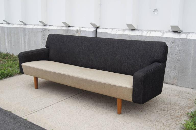 The strong, clean lines of the AP33 sofa, designed by Hans Wegner for A.P. Stolen in the mid-1950s, make it a perfect fit for a contemporary environment. Set on oak legs and upholstered in contrasting textiles, this sofa looks attractive from all
