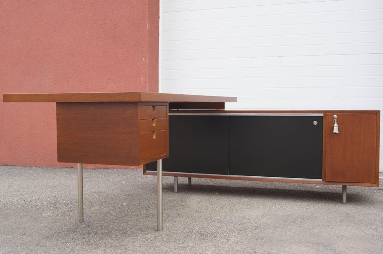 Mindful of the needs of architecture firms and other creative environments, George Nelson designed this tawny walnut desk and storage unit as part of Herman Miller's Executive Office Group. A free-floating work surface (7230-L) with a three-drawer