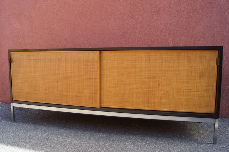 This sideboard exemplifies Florence Knoll's classic clean-lined aesthetic. The black laminate case sits on a steel base and features handsome cane sliding doors with leather pulls. Inside are four tray drawers, one filing drawer, and adjustable