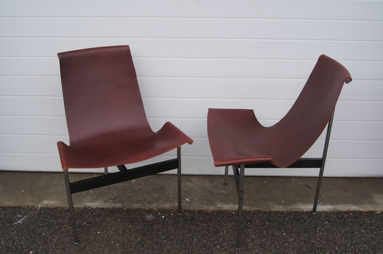 William Katavolos in partnership with Douglas Kelley & Ross Littell designed the iconic sling-back T chair in 1952 as model 3LC in Laverne International's sculptural New Furniture series. Hidden screws attach the leather seat to a frame of chromed
