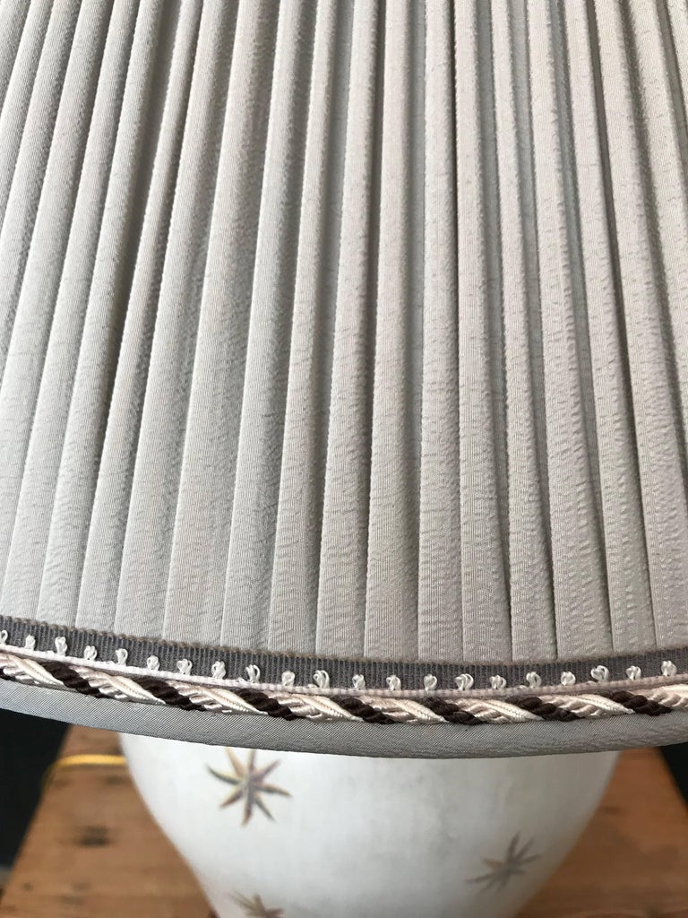 Star design in wood ginger jar base. Gray pleated shade with trim.