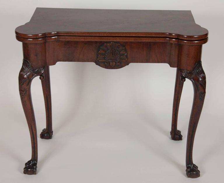 A fine walnut George I period table with a central shell carving and concertina opening action. Turreted top corners over a central carved shell, carved shell cabriole legs molded and ending on ball and claw feet.