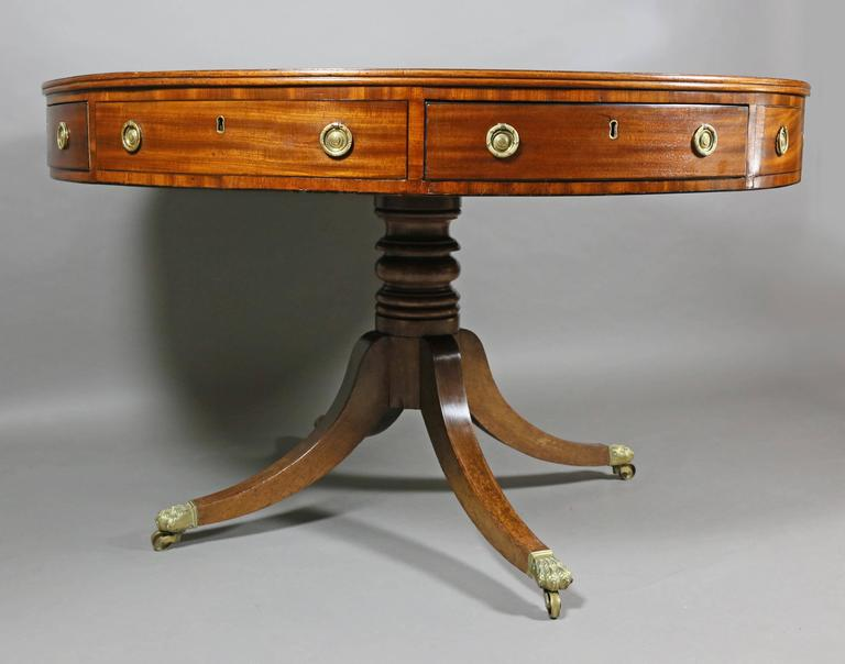 Circular inset blackish blue leather top over a series of false and working drawers raised on a ring turned support and four saber legs ending in paw from cup casters.