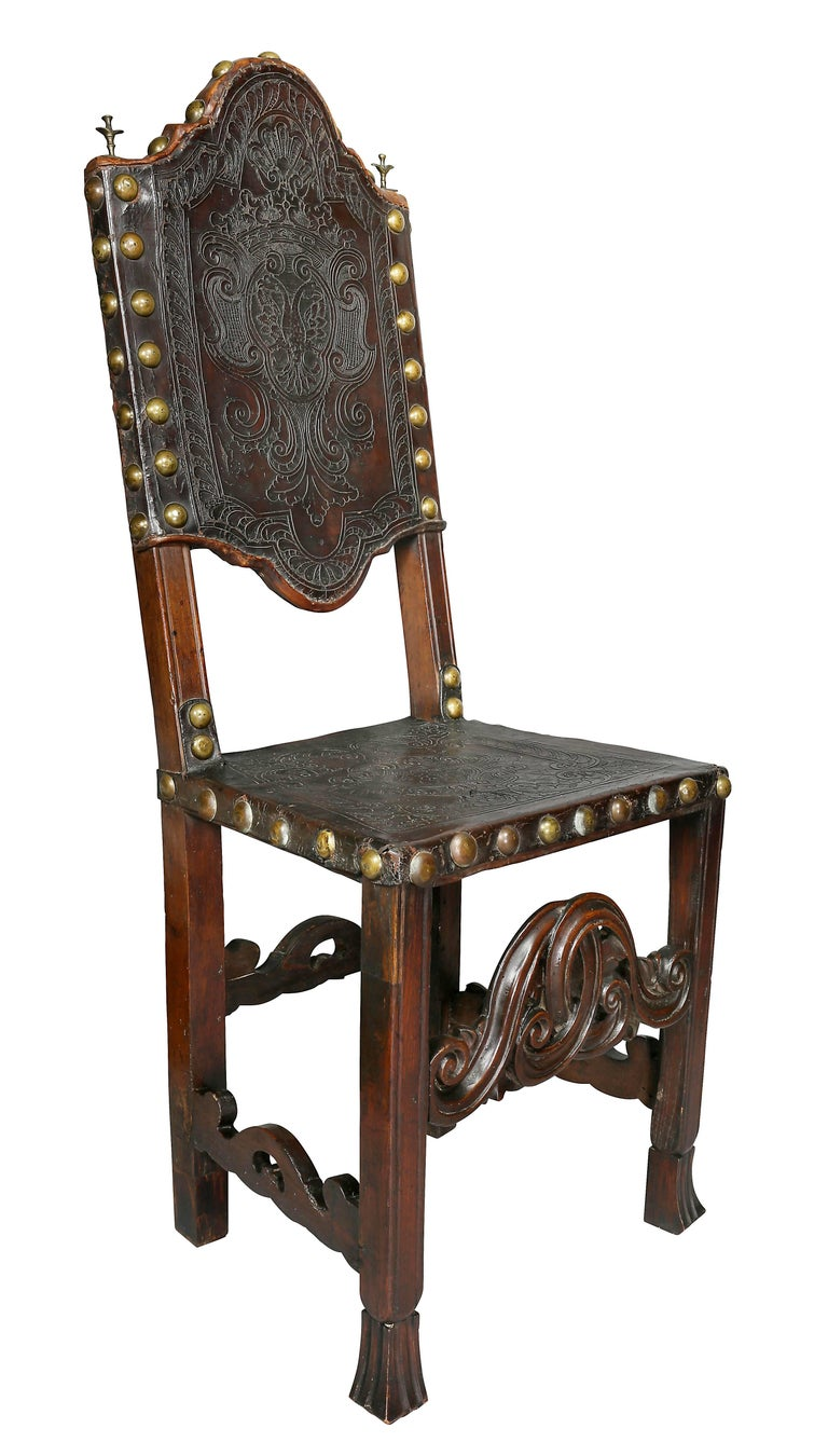 Each with arched embossed leather backs and square seats raised on molded legs with carved stretchers.