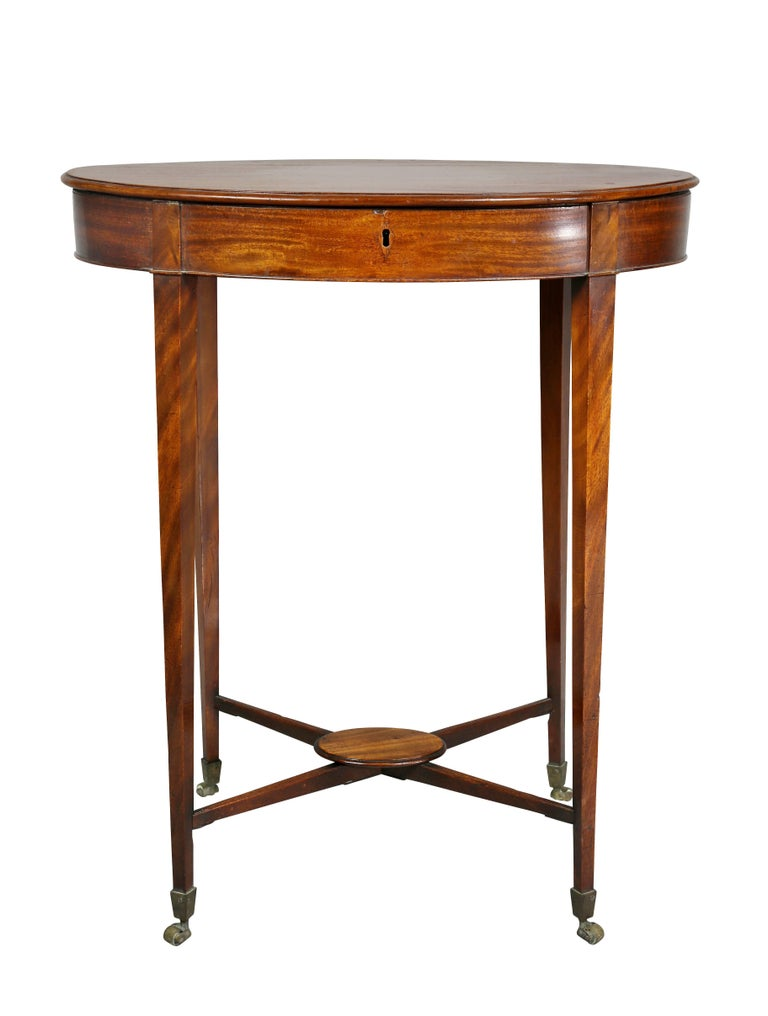 Oval with hinged top raised on square tapered legs with X shaped stretcher, casters.