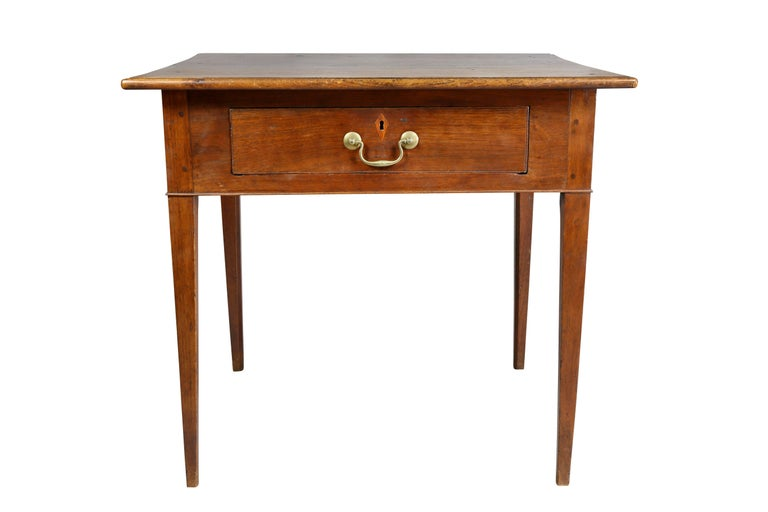 Rectangular top over a single drawer with inlaid escutcheon and original bail handle raised on square tapered legs.