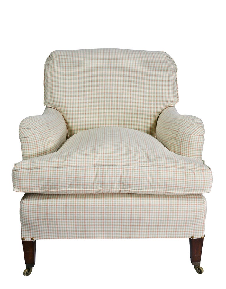Upholstered scrolled back and shaped arms, loose cushion, square tapered legs with brass casters.