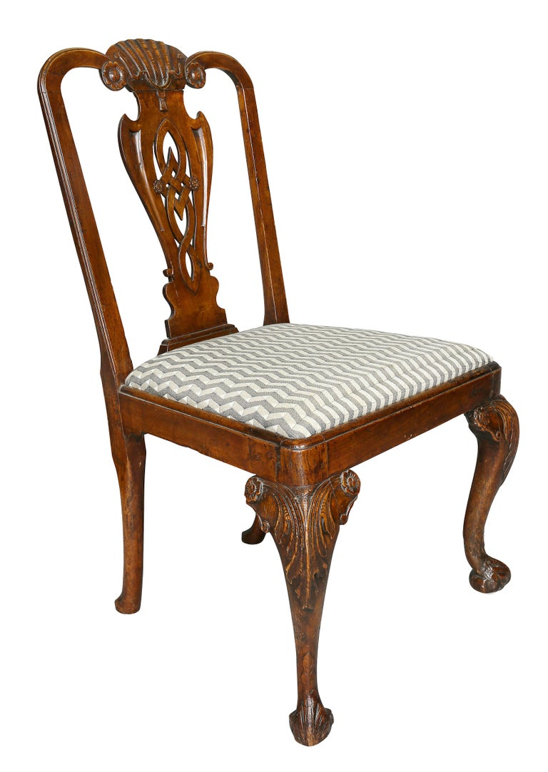 With carved shell and tassel crest rail over a pierced vasiform splat, drop in seat, raised on cabriole legs and scroll feet.