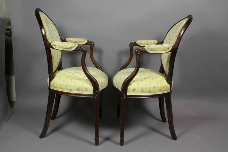 Oval upholstered back with oval carved paterae and bellflower crestrail , carved downswept arms and serpentine upholstered seat raised on stop fluted tapered square legs , spade feet.