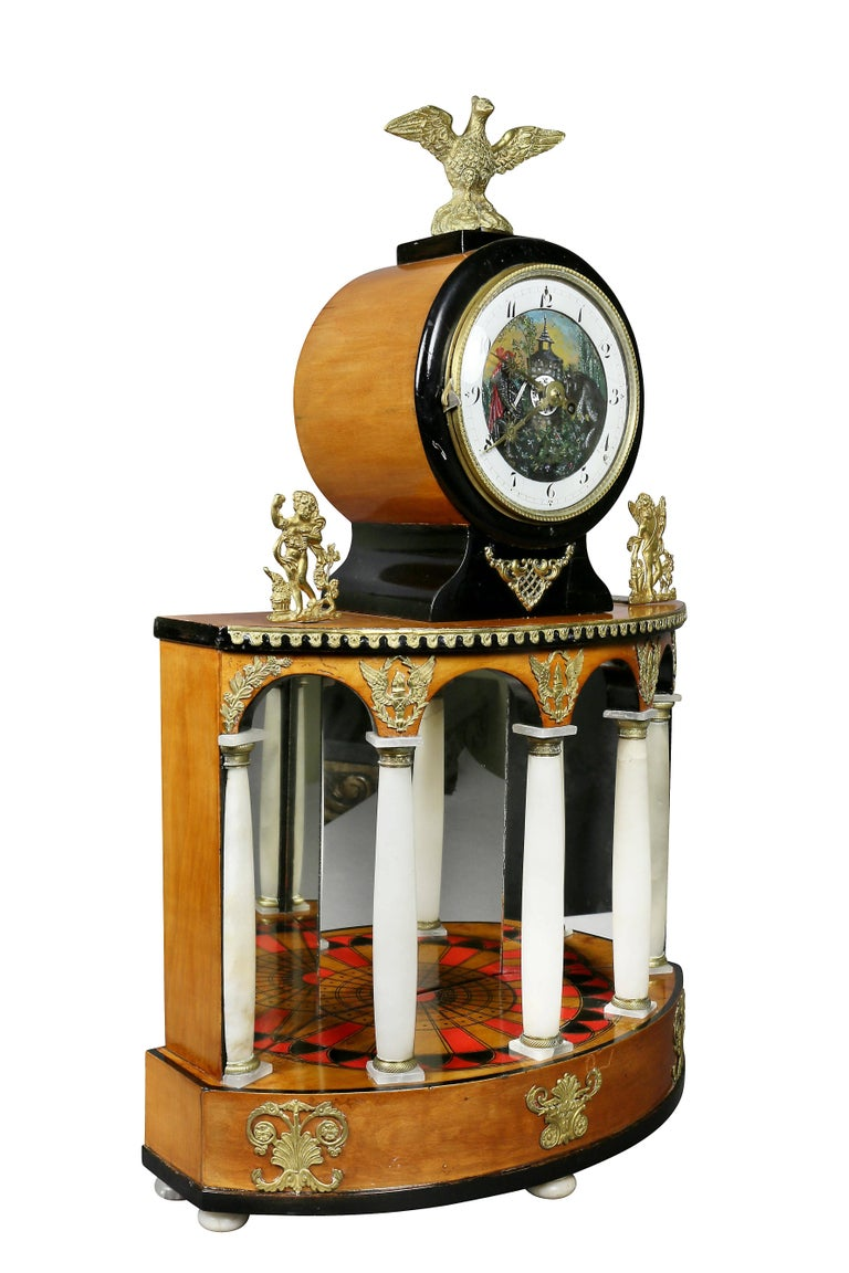 With eagle finial over an enameled and painted clock face over an inlaid portico with mirror back and alabaster columns on a plinth base.